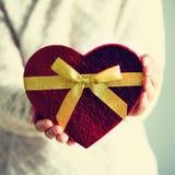 Les mains femelles tenant le coeur de boîte-cadeau forment sur le fond gris Copiez l'espace Concept d'amour Collecte carrée Photo stock