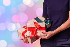 Les mains femelles tiennent des cadeaux au fond de bokeh images stock