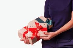 Les mains femelles tiennent des cadeaux pendant des vacances de Noël photographie stock libre de droits