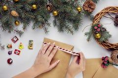 Les mains femelles tiennent la carte et l'enveloppe de Joyeux Noël Fond de décoration de Noël Configuration plate, vue supérieure photos stock