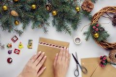 Les mains femelles tiennent la carte et l'enveloppe de Joyeux Noël Fond de décoration de Noël Configuration plate, vue supérieure photographie stock libre de droits
