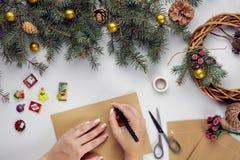 Les mains femelles tiennent la carte et l'enveloppe de Joyeux Noël Fond de décoration de Noël Configuration plate, vue supérieure photo libre de droits