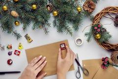 Les mains femelles tiennent la carte et l'enveloppe de Joyeux Noël Fond de décoration de Noël Configuration plate, vue supérieure images stock