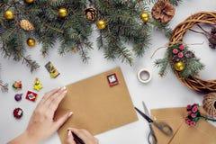 Les mains femelles tiennent la carte et l'enveloppe de Joyeux Noël Fond de décoration de Noël Configuration plate, vue supérieure photo stock