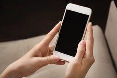 Les mains femelles tiennent le t?l?phone blanc dans leurs mains Plan rapproch? de t?l?phone portable photo stock