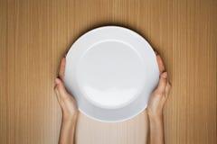 Les mains femelles tiennent un plat blanc vide Photos stock