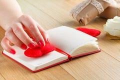 Les mains femelles touchent le coeur rouge sur le journal intime pour la Saint-Valentin avec g Photo stock