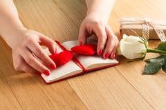 Les mains femelles touchent le coeur rouge sur le journal intime pour la Saint-Valentin avec g Images libres de droits