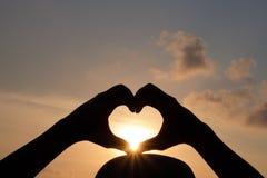 Les mains font une forme de coeur pour laisser le soleil passer  Images libres de droits