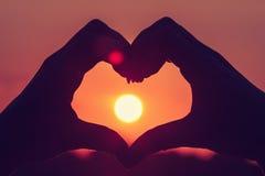 Les mains formant un coeur forment avec la silhouette de coucher du soleil Photos stock