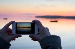Les mains gardant le téléphone et prennent la photo du coucher du soleil de clour Images stock