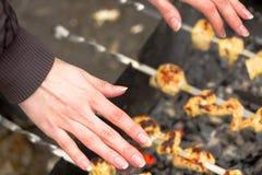 Les mains gelées de la fille au-dessus du gril avec le barbecue images stock