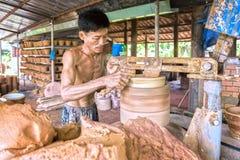 Les mains habiles traînent au travail formant les produits en céramique Image libre de droits