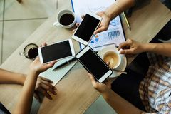 Les mains humaines emploient le contact mobile ensemble, le travail d'équipe d'affaires avec le téléphone portable et le diagramm images libres de droits