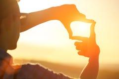 Les mains humaines faisant un cadre signent plus de le ciel de coucher du soleil images stock