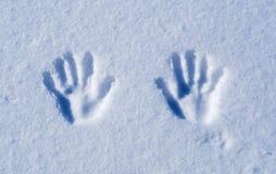 Les mains impriment sur la neige claire au soleil images stock