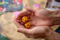 Les mains jette les matrices jaunes sur le champ de jeu Chance et excitation Concept des jeux de soci?t? Moments de jeu dans la d images stock