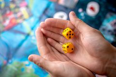 Les mains jette les matrices jaunes sur le champ de jeu Chance et excitation Concept des jeux de soci?t? Moments de jeu dans la d photographie stock