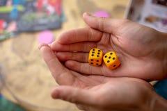 Les mains jette les matrices jaunes sur le champ de jeu Chance et excitation Concept des jeux de soci?t? Moments de jeu dans la d photos libres de droits