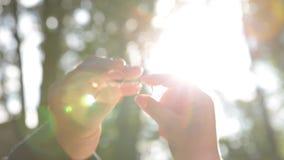 Les mains jugent des anneaux étroits contre les rayons du soleil Évaluant des bijoux ou obtenant marié banque de vidéos