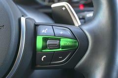 Les mains libèrent et les boutons de contrôle de media sur volant dedans le cuir noir, détails modernes d'intérieur de voiture Photographie stock