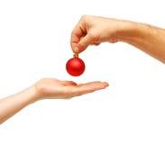 Les mains mâles donnent une bille de Noël aux mains femelles images stock