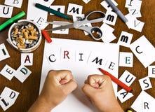 Les mains mâles ont remonté des lettres dans le mot - crime. Photographie stock libre de droits