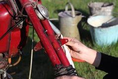 Les mains mécaniques nettoie son pionnier rouge de Jawa de motocyclette démodée Vélo de rénovation après des années dans la cave  photo stock