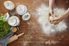 Les mains malaxant la pâte flour sur l'espace de travail en bois de cuisine Photographie stock libre de droits