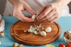 Les mains masculines épluche les oeufs de caille bouillis de la coquille sur la planche à découper en bois dans la cuisine photo stock