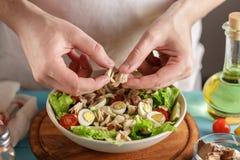 Les mains masculines ajoute des morceaux de conserve de thon dans la cuvette avec d'autres ingrédients frais photo libre de droits
