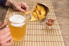 Les mains masculines de table en bois tenant une tasse avec de la bière et des nachos ont plongé à la sauce Copiez la pâte photos libres de droits