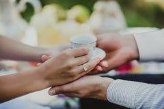 Les mains masculines et femelles avec une tasse et une soucoupe, la conception de la date et les pauses-café, mariage dans l'amou Photographie stock