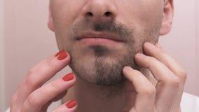 Les mains masculines et femelles touchent le visage de sourire après le rasage banque de vidéos