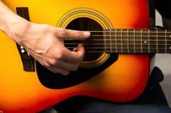 Les mains masculines jouant la guitare acoustique, se ferment  Photographie stock libre de droits