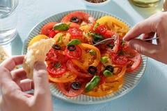 Les mains masculines mangent de la salade de tomate avec le morceau de pain avec une fourchette images libres de droits