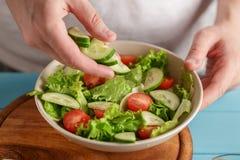 Les mains masculines mises ont coupé en tranches le concombre dans la cuvette avec les légumes frais photographie stock