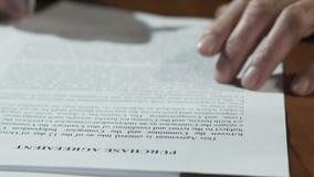 Les mains masculines signant l'achat s'occupent des documents sur la table, propriété d'appartement banque de vidéos