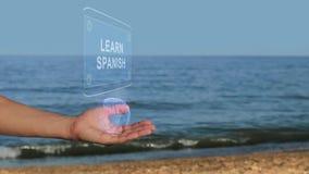 Les mains masculines sur la plage tiennent un hologramme conceptuel avec le texte apprennent espagnol banque de vidéos