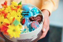 Les mains masculines tenant le boîte-cadeau ont rempli de fleurs et de sucrerie de fruit Photographie stock libre de droits