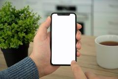 Les mains masculines tenant le contact noir téléphonent avec l'écran Photo libre de droits