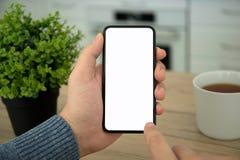 Les mains masculines tenant le contact noir téléphonent avec l'écran d'isolement Image stock