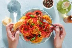 Les mains masculines tiennent la fourchette et le morceau de pain pour et de salade tout préparée de tomate photos libres de droits