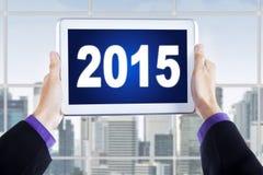 Les mains masculines tiennent le comprimé numérique avec le numéro 2015 Image libre de droits