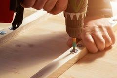 Les mains masculines vissent les blocs en bois aux conseils avec un tournevis images libres de droits