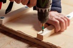 Les mains masculines vissent les blocs en bois aux conseils avec un tournevis photos stock