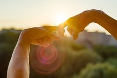 Les mains montrent le geste des doigts ensemble, le symbole de l'amitié et les relations Coucher du soleil de soirée de fond, sil photographie stock libre de droits