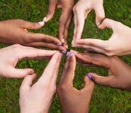 Les mains noires et blanches au coeur forment, concept interracial d'amitié Image libre de droits