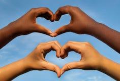 Les mains noires et blanches au coeur forment, concept interracial d'amitié Image stock