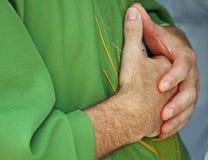 Les mains ont étreint dans la prière le prêtre avec la robe photos libres de droits